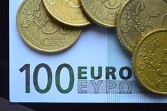 En valör av 100 euro och mynt fördelade på den Arkivfoto