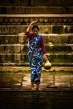 En vallfärda badar och wash i det heliga vattnet av Gangesen, Varana Arkivbild