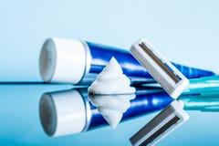 En vanlig disponibel rakkniv och en raka kräm- närbild i badrum på en reflekterande yttersida för exponeringsglas mot en blå bakg arkivfoton