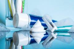 En vanlig disponibel rakkniv och en raka kräm- närbild i skumet i ett modernt badrum på en reflekterande yttersida för exponering arkivfoton