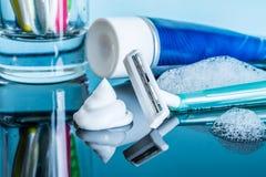 En vanlig disponibel rakkniv och en raka kräm- närbild i skumet i ett modernt badrum på en reflekterande yttersida för exponering royaltyfri foto