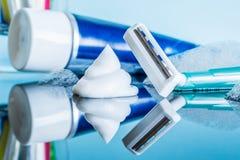 En vanlig disponibel rakkniv och en raka kräm- närbild i skumet i ett modernt badrum på en reflekterande yttersida för exponering fotografering för bildbyråer