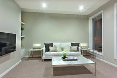 En vardagsrum med en liten vit tabell och kuddar p? soffan royaltyfri foto