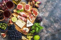 En variation av aptitretaren, prosciutto, druvor, vin, ost med formen, fikonträd, oliv på en lantlig bakgrund Medelhavs- mellanmå royaltyfri foto