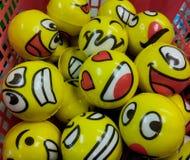 En variation av Emoji vänder mot på gula bollar i en korg på ett krimskramslager i nytt - ärmlös tröja, redaktörs- bruk Royaltyfri Fotografi