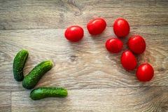 En variation av grönsaker lade ut färgerna av en trätabletop royaltyfria foton