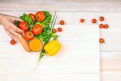 En variation av healthful grönsaker - moroten, peppar, gör grön på en ljus bakgrund En hand som rymmer en smaklig tomat Royaltyfria Foton