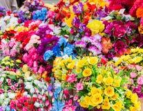 En variation av konstgjorda blommor Färgrik bakgrund av blommor Arkivbild