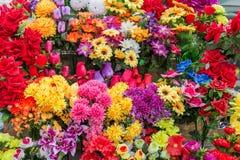 En variation av konstgjorda blommor Färgrik bakgrund av blommor Royaltyfria Bilder