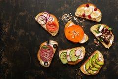 En variation av rostat bröd med grönsaker, frukter, laxen och korven på en mörk bakgrund, bästa sikt Smörgåsar med en variation a royaltyfria bilder