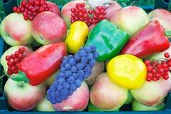 En variation av stora mogna frukter och grönsaker i behållaren Arkivbilder