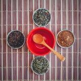 En variation av teer och en träsked i en tom röd kopp Arkivfoton
