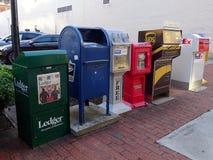 En variation av tidningsställningar och brevlådor som lokaliseras på en stadsgata i Knoxville Arkivfoton