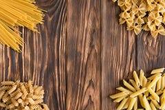 En variation av variationer av pasta på en härlig trätabell Royaltyfri Fotografi