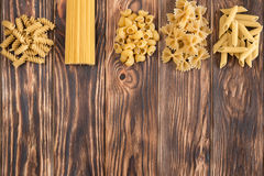 En variation av variationer av pasta på en härlig trätabell Royaltyfri Bild