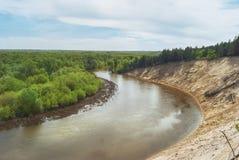 En varm vårdag i skogdalen av den ryska floden med en brant sandig lutning Landskap arkivfoto