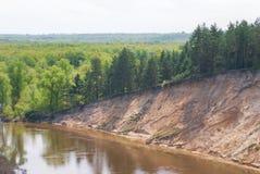 En varm vårdag i skogdalen av den ryska floden med en brant sandig lutning Landskap royaltyfri fotografi