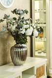 En vas av blommor på tabellen med en spegel arkivbild