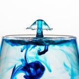 En vattendroppe plaskade in i ett exponeringsglas med blåttfärg arkivbilder