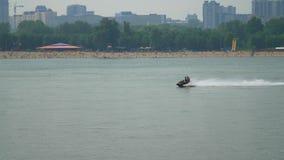 En vattenmotorcykel rider längs floden, mot bakgrunden av stranden stock video
