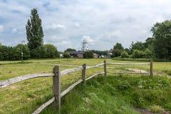 En väderkvarn som ses i avståndet av floden Rother som ses i råg, Kent, UK Royaltyfri Fotografi