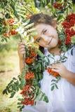 En verano, cerca del arbusto de la ceniza de montaña hay una niña imagen de archivo