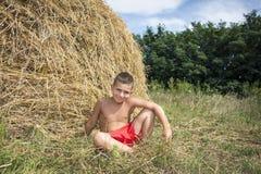 En verano, cerca del pajar, un chico del campo se sienta Foto de archivo