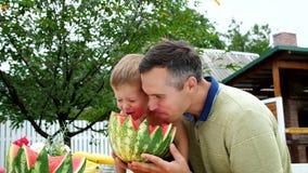 En verano, en el jardín, el padre con un hijo de cuatro años cortó una sandía y la come, se divierte, un muchacho le gusta la san metrajes