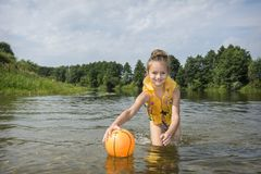 En verano, en el río, una muchacha en un chaleco juega con una bola imagen de archivo libre de regalías