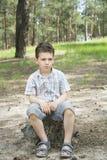 En verano, en un bosque del pino en un tocón de árbol sienta al muchacho triste Fotografía de archivo