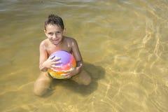 En verano, en un brillante, día soleado, un muchacho en el río juega con Fotos de archivo