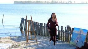 En verano, en la orilla del río, en la playa en el amanecer, un artista hermoso de la mujer, en un traje apretado, ella baila, sa almacen de video