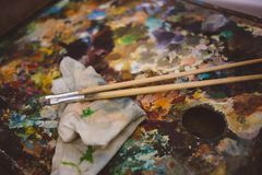 en verklig artist& x27; s-palett, oljamålarfärger och två målarfärgborstar arkivbild