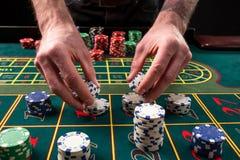 En vibrerande bild för närbild av den gröna kasinotabellen med rouletten, med händerna av croupier och mångfärgade chiper fotografering för bildbyråer