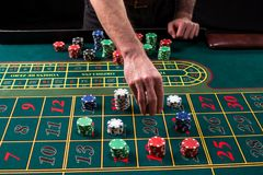 En vibrerande bild för närbild av den gröna kasinotabellen med rouletten, med händerna av croupier och mångfärgade chiper royaltyfria bilder