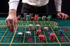 En vibrerande bild för närbild av den gröna kasinotabellen med rouletten, med händerna av croupier och mångfärgade chiper royaltyfria foton