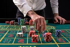 En vibrerande bild för närbild av den gröna kasinotabellen med rouletten, med händerna av croupier och mångfärgade chiper royaltyfri foto