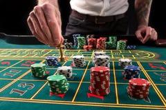 En vibrerande bild för närbild av den gröna kasinotabellen med rouletten, med händerna av croupier och mångfärgade chiper arkivfoto