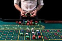 En vibrerande bild för närbild av den gröna kasinotabellen med rouletten, med händerna av croupier och mångfärgade chiper royaltyfri bild