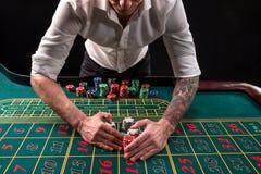 En vibrerande bild för närbild av den gröna kasinotabellen med rouletten, med händerna av croupier och mångfärgade chiper royaltyfri fotografi