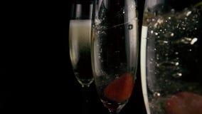En vidrios con caída de las fresas del champán MES lento metrajes