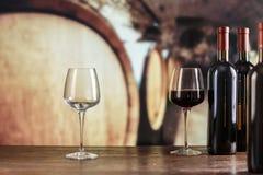 En vidrios de vino rojo en un fondo de barriles grandes Imagen de archivo