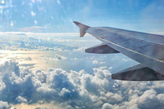 En vinge av flygplanet ovanför molnen Arkivbild