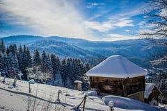 En vinter och en solig dag på berget Gammal huscloseup och härliga vinterlandskap, blå himmel och moln i bakgrunden royaltyfri bild
