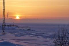 En vintersolnedgång över en stor fryst sjö På långt banken i ogenomskinligheten är synliga konturer av byggnader En tyst frostig  Royaltyfri Bild