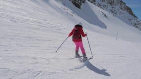 En vista lateral del movimiento, esquiador de la mujer que esquía cuesta abajo del centro turístico de montaña almacen de video