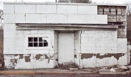 En vit övergiven byggnad vid sidan av vägen på en molnig dag med ett brutet fönster som göras av tegelsten Royaltyfri Bild