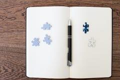 En vit anteckningsbok på en trätabell med två pusselstycken och a arkivbilder