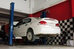 En vit bil lyfts upp för den reparera processen på garaget arkivfoton