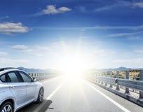 En vit bil som rusar längs en snabb huvudväg i solen arkivbild